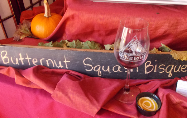 Sign for Butternut Squash Bisque with wine glass and sample of the bisque