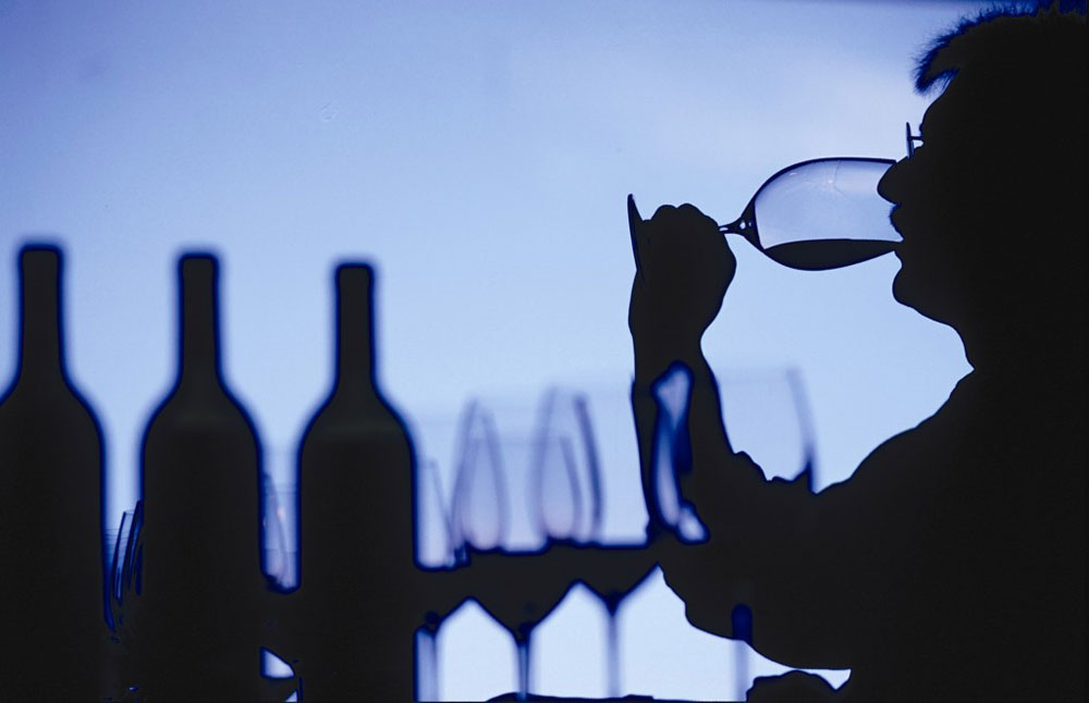 silhouette of a man sipping from a wine glass