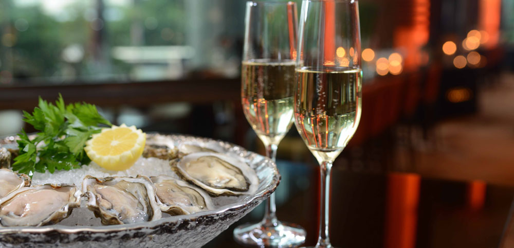 Two champagne flutes and a plate of raw oysters