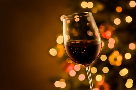 Glass of red wine with Christmas lights behind