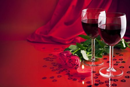 Two glasses of red wine on a red background with red roses and a heart shaped candle