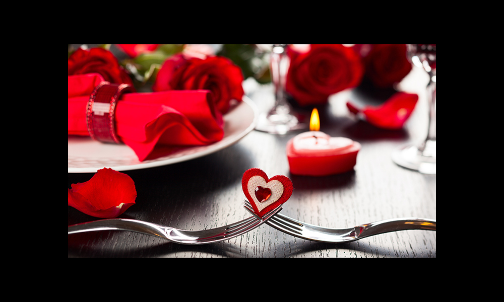 Valentie's photo of two forks intertwined with heart placed where they meet. Flowers and candles in the background.