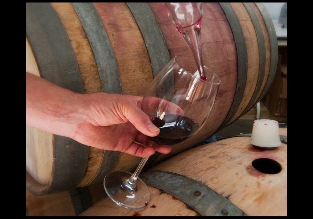 Using a wine thief, wine is siphoned out of the barrel and into an awaiting wine glass.