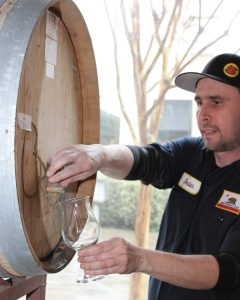 A man pouring spirits from a barrel into a special spirit tasting glass