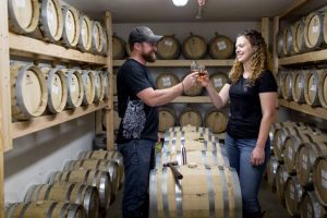 a male and female tasting cider surrounded by barrels of cider
