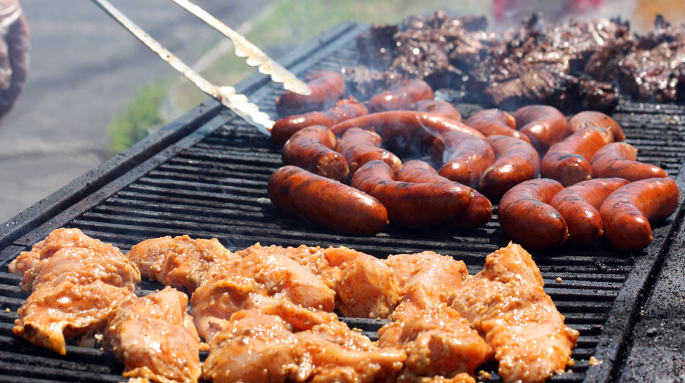 various meats cooking on a large outdoor grill