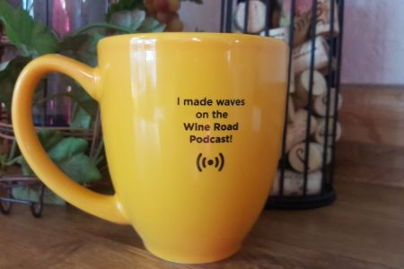 "mug with writing that reads ""I mad waves on the Wine Road podcast!"""