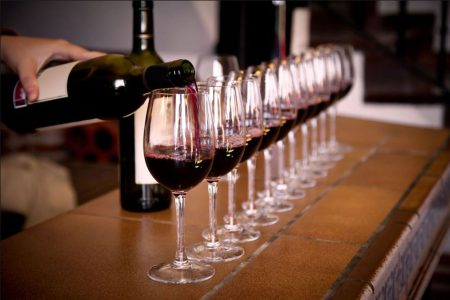 line of glasses being poured with red wine
