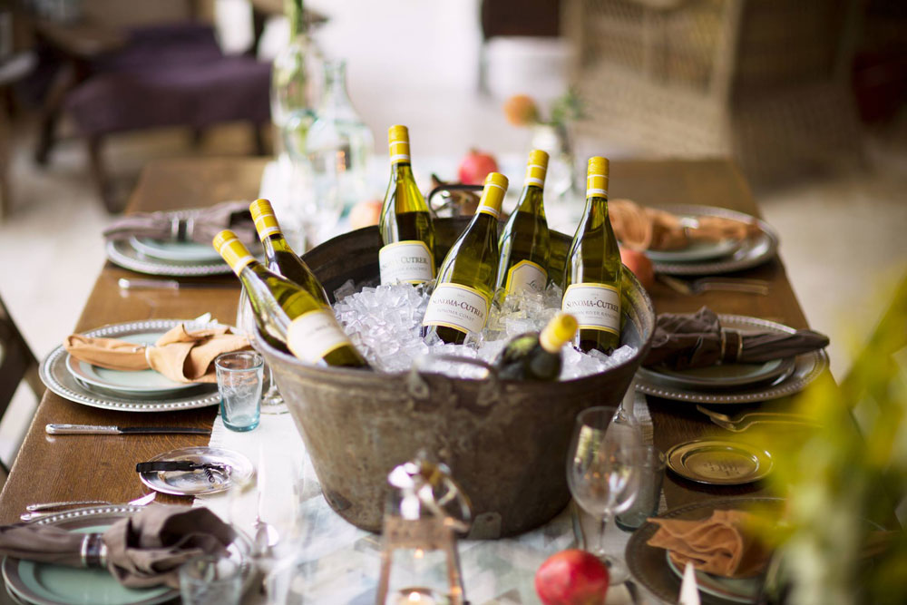 Table set for a meal with a ice bucket filled with Sonoma Cutrer Chardonnay