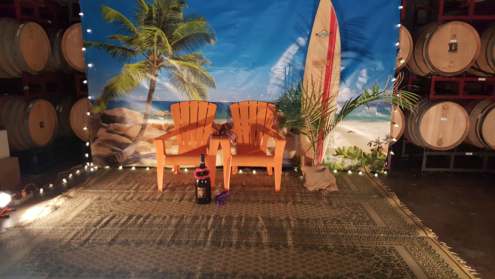 A tropical backdrop hung in from of stacked wine barrels with two lawn chairs, a surf board and a bottle of wine.