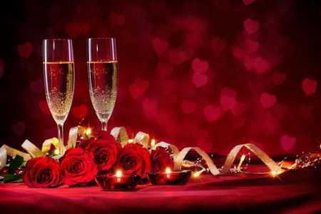 Two flutes filled with sparkling wine and set among red roses, gold ribbon and votive candles.