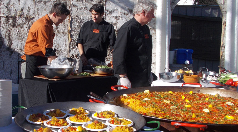 Paella being cooked and served at a winery event.