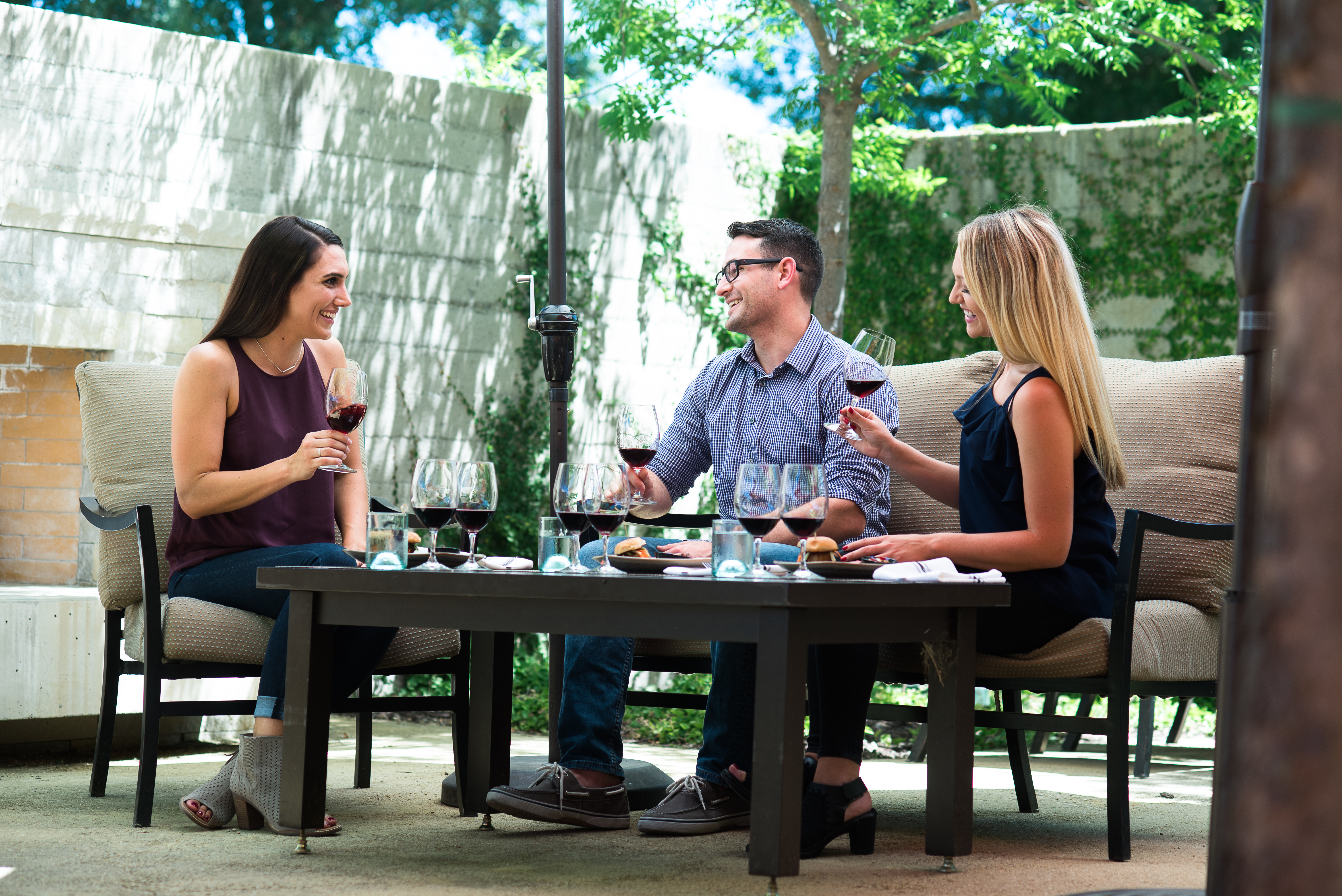 Two woman and a man enjoy a food and wine pairing in a courtyard area.