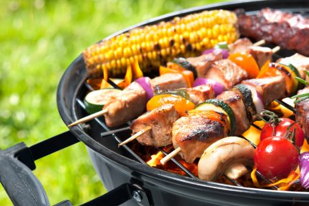 A kettle barbecue grill filled with kebabs of meat and veggies, plus corn on the cob