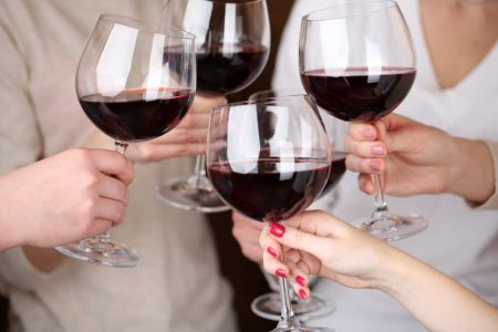 Friends toasting with glassed filled with red wine