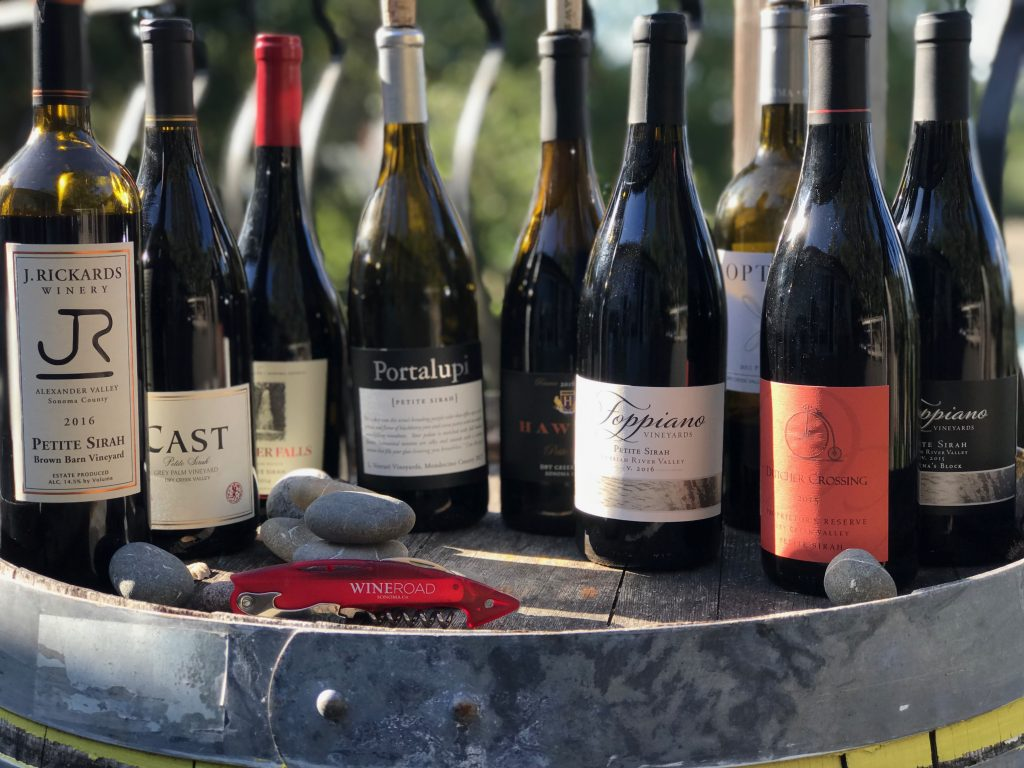 Bottles of Petite Sirah in the sun on a wine barrel with a red corkscrew