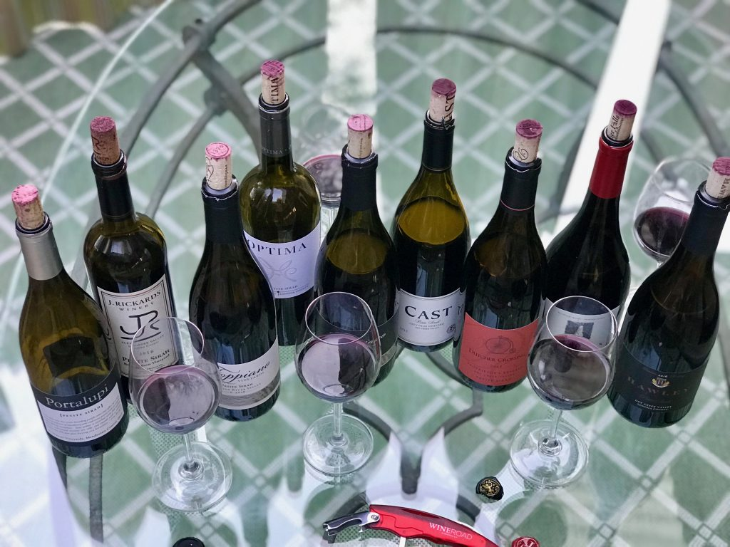 A wide selection of Petite Sirah on a glass table looking down from above.