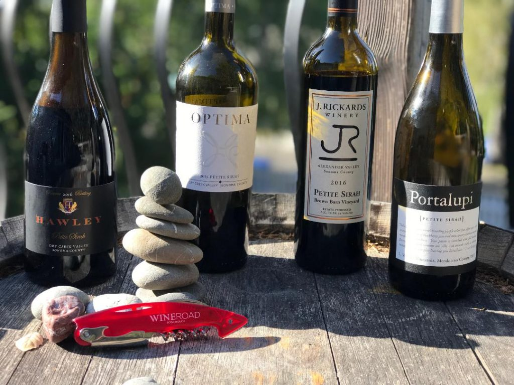 Bottle of Petite sirah on a barrel with rocks and a red corckscrew
