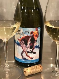"""Bottle of Mutt Lynch """"Pure Joy on the Beach"""" Roussanne with with happy dog on the label and glass in front of bottle"""