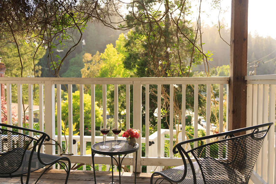Two glasses of wine on a small deck table surround by chairs and a garden view.