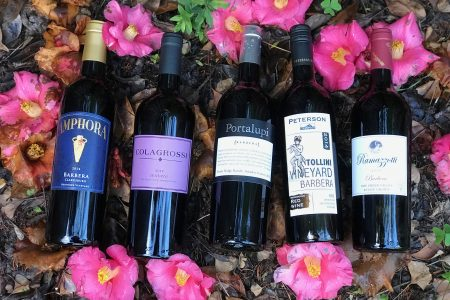 Bottles of Barbera wine sitting next to pink flowers