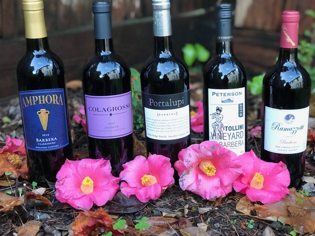bottles of Barbera on the ground next to pink flowers