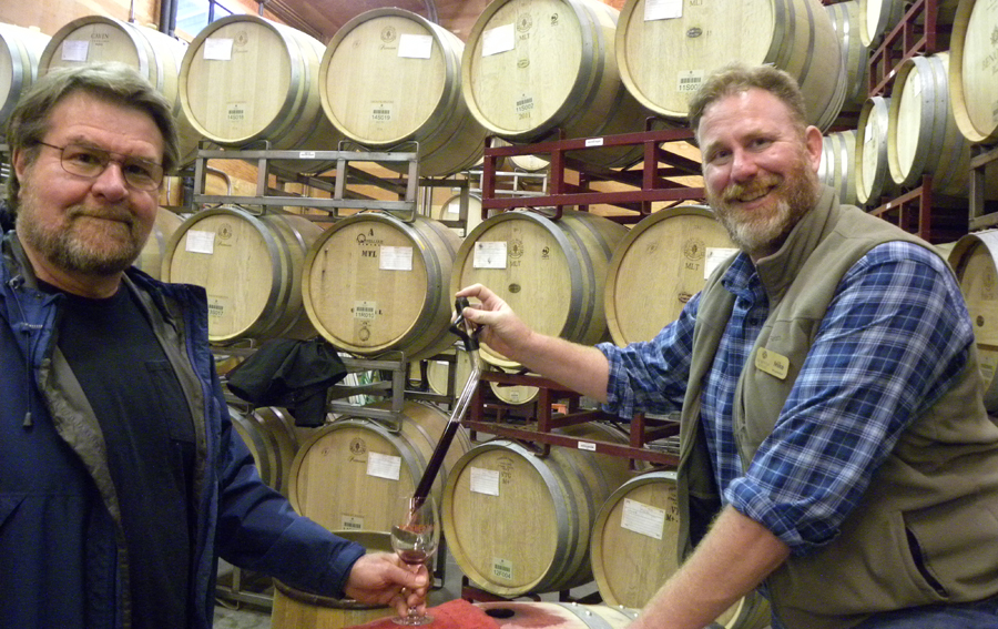 Benovia's winemaker and co-owner Mike Sullivan pouring wine from a barrel of Pinot Noir using a wine thief.