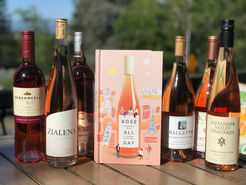 Bottles of Rose with book Rose All Day on a table outside