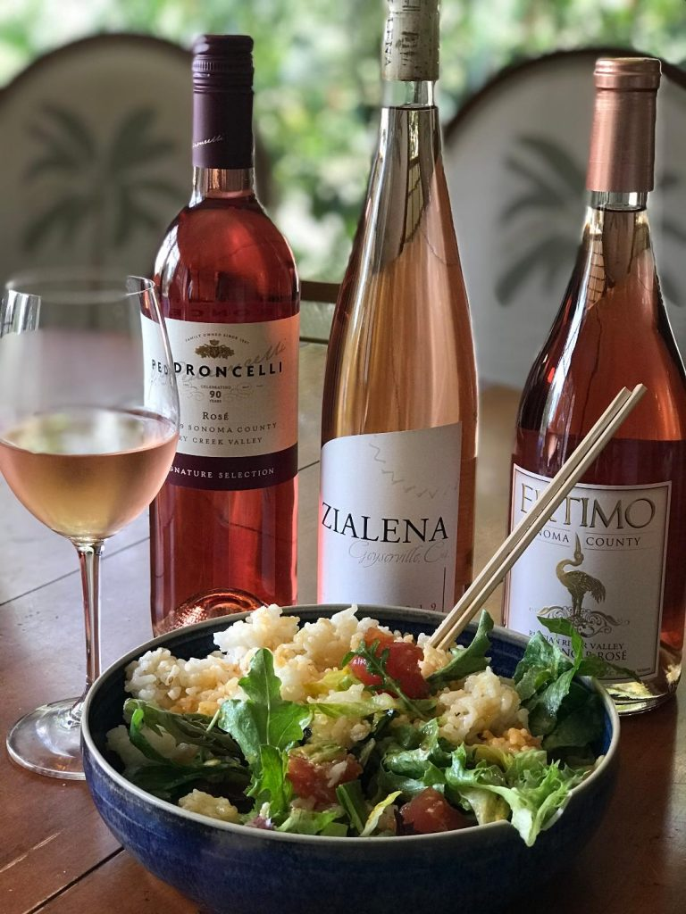 Three bottles of Rose wine and a tuna poke bowl on a table with a glass of rose