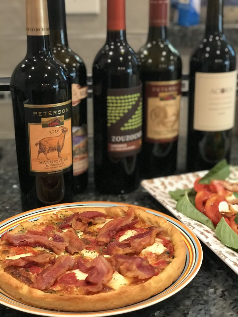 Pizza and salad with Sangiovese bottles in background