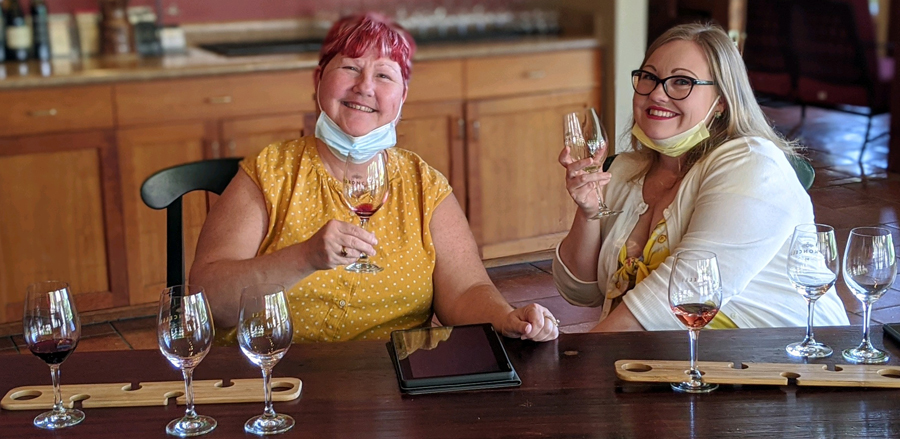 Two woman tasting wine flights with a tablet between them.