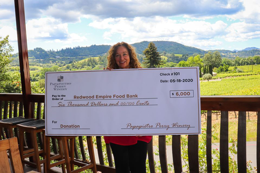 Renae Perry, co-owner of Papapietro Perry Winery, holds a $6000 check for the Redwood Empire Food Bank. A donation from wine sales.