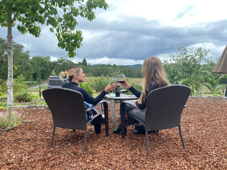 Two woman seated toast wine glasses as they look out on a lovely vineyard view.