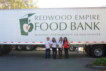 Redwood Empire Food Bank semi-truck with four people standing below the side of the truck.
