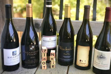 Bottles of Pinot Noir on a deck with blocks spelling out Pinot Noir