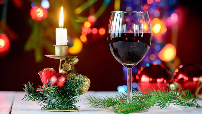 Glass of red wine with holiday decorations around and behind it.